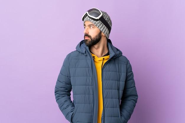 Uomo in abiti invernali sulla parete pastello