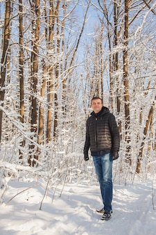 Uomo in pineta invernale con neve sugli alberi e sul pavimento in una giornata di sole.