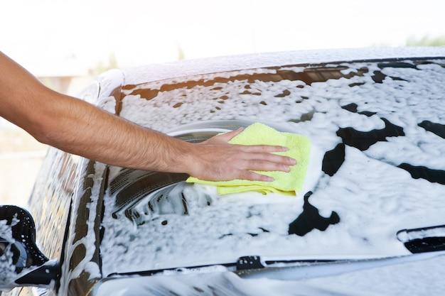 Un uomo pulisce la schiuma sull'auto con uno straccio. autolavaggio