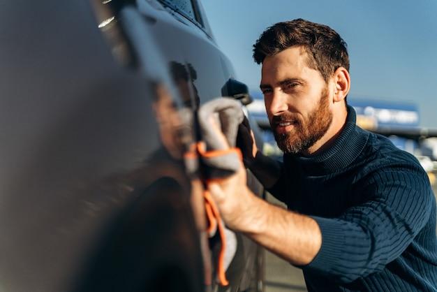 Uomo che pulisce la sua auto in strada. lavaggio dei dettagli dell'auto durante la giornata di sole. bell'uomo barbuto in abbigliamento casual che lava le portiere e il cofano dell'auto con un panno in microfibra
