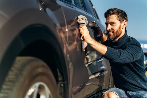 Uomo che pulisce la sua auto in strada. vista ravvicinata del bell'uomo barbuto in abbigliamento casual che lava le portiere e il cofano dell'auto con un panno in microfibra. lavaggio dei dettagli dell'auto durante il concetto di giornata di sole