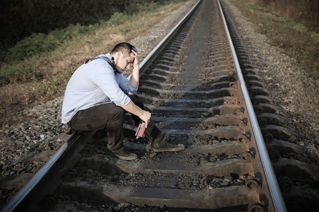 Uomo con alcol sui binari ferroviari all'aperto. malattia della depressione. crisi economica, povertà, concetto di disoccupazione. conseguenze dell'isolamento delle persone con coronavirus durante la quarantena. senza speranza.