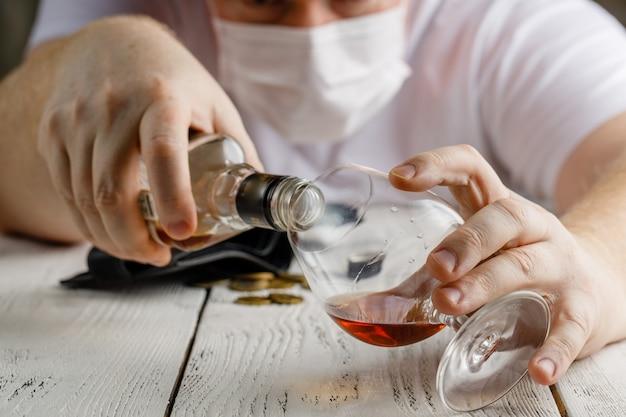 Uomo con alcool indossando maschera medica. corona virus concept