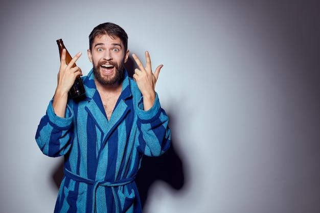 Uomo con bevanda alcolica in una bottiglia e in una veste blu su una luce