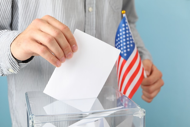 Uomo con la bandiera americana mettendo scheda elettorale nella casella di voto
