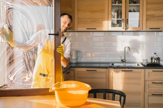 Uomo con la finestra di pulizia del grembiule