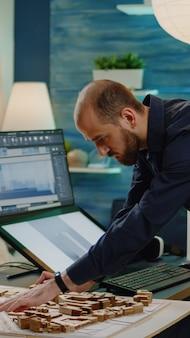 Uomo con lavoro di architetto che lavora su un modello di edificio