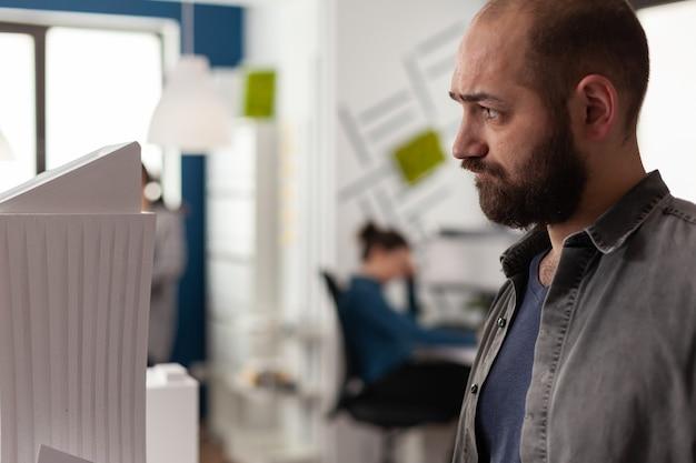 Uomo con professione di architetto che lavora in ufficio sulla costruzione del modello di progettazione maquette sul tavolo caucasico...