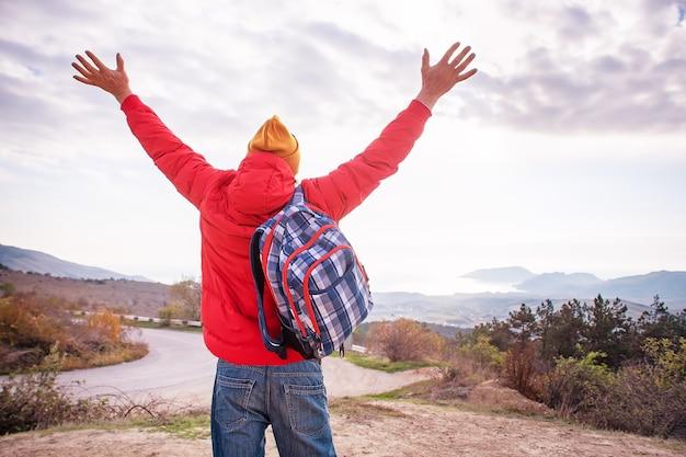 L'uomo con la vista posteriore dello zaino ha alzato le mani con il paesaggio di montagna