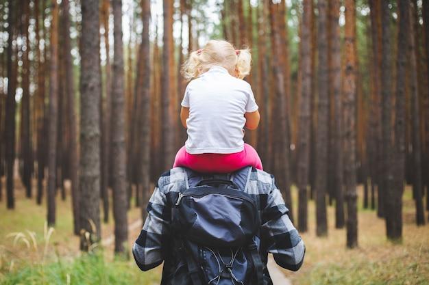 L'uomo con uno zaino porta un bambino sulle spalle nella foresta. escursione in famiglia in montagna o nella foresta.