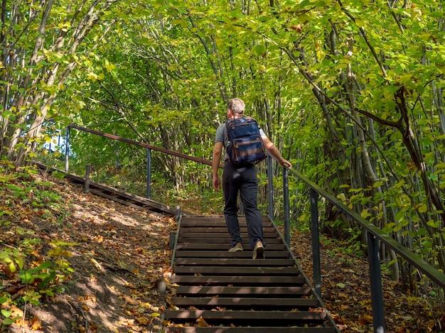 Un uomo con uno zaino si arrampica sul sentiero