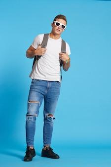 Un uomo con uno zaino in occhiali e in jeans maglietta blu muro in piena crescita