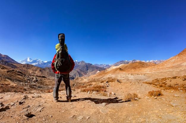 Un uomo con uno zaino e una chitarra si alza e guarda romanticamente le montagne del nepal. retrovisore.