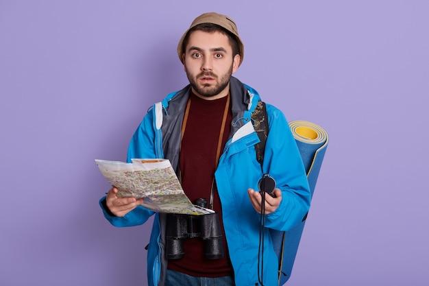 Uomo con zaino e indicazioni stradali per la ricerca della mappa