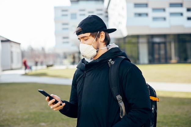 Uomo con zaino e maschera protettiva che usa il telefono per strada, giovane millenario con il telefono in mano mentre coronavirus in piedi all'aperto