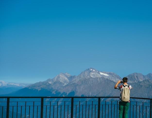 Uomo con zaino in piedi sul ponte di osservazione in montagna