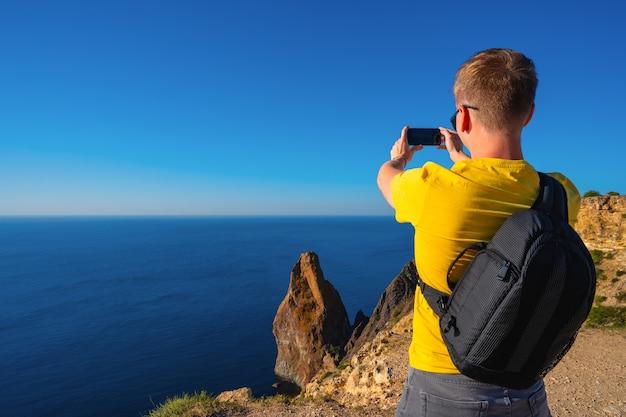 Un uomo con uno zaino scatta foto con uno smartphone della vista delle rocce e dell'azzurro del mare