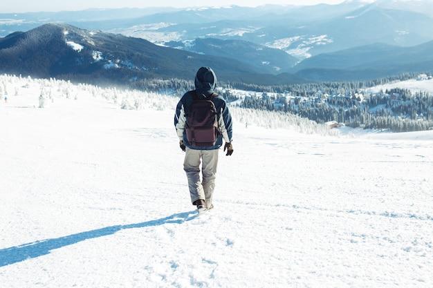 Uomo con zaino da trekking in montagna. tempo freddo, neve sulle colline. escursioni invernali. l'inverno sta arrivando, prima nevicata. concetto di viaggio, riposo, relax