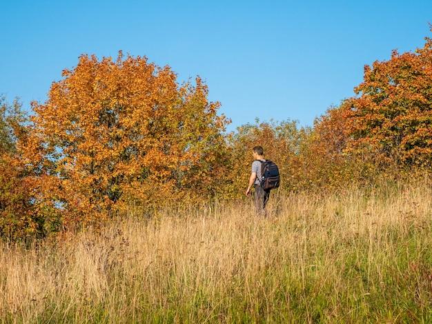 L'uomo con uno zaino durante un viaggio di trekking in autunno scende dalla collina in autunno