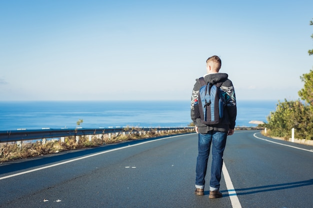 Un uomo con uno zaino cammina da solo su una strada di montagna