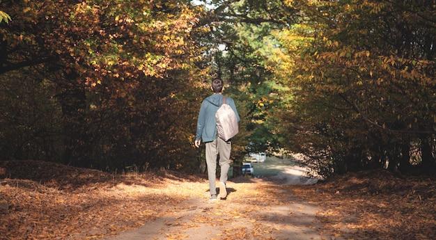 L'uomo con uno zaino cammina attraverso la foresta. autunno