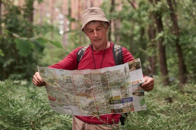Uomo con zaino, indossa maglione casual rosso e cappello lettura mappa nei boschi.