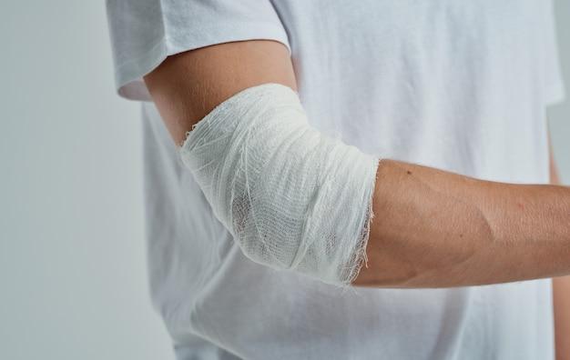 Uomo con il gomito del braccio bendato e la medicina di lesioni al dito