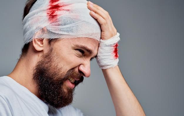 Un uomo con una garza del modello di chirurgia di rianimazione del sangue alla testa fasciata sul braccio