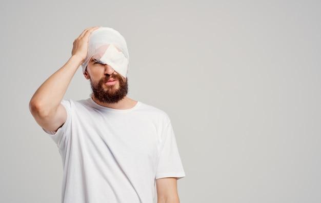Uomo con ricovero in ospedale per problemi di salute alla testa fasciata.