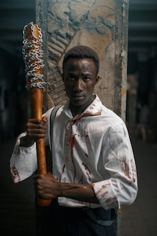 Uomo con mazza da baseball, inseguimento mortale di zombie in una fabbrica abbandonata. orrore in città, attacchi di striscianti raccapriccianti, apocalisse del giorno del giudizio, mostro sanguinante