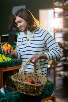 Uomo con i canestri che selezionano peperone dolce nella sezione organica