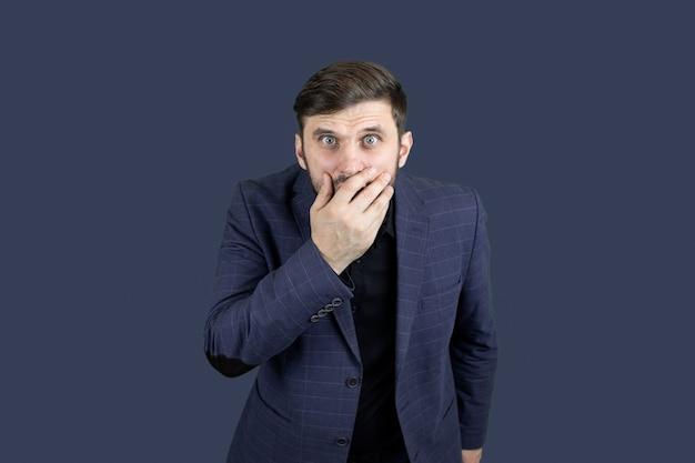 Un uomo con la barba e un vestito blu si coprì la bocca con la mano