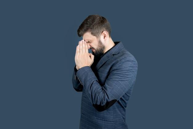 Un uomo con la barba e un abito blu incrociò le mani, i palmi rivolti l'uno verso l'altro