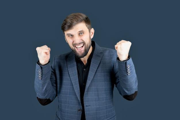 Un uomo con la barba e un vestito blu ha alzato i pugni in aria mostrando le emozioni della vittoria
