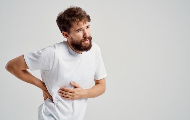 Un uomo con la barba che gesticola con le mani carico della colonna vertebrale dolore alla schiena