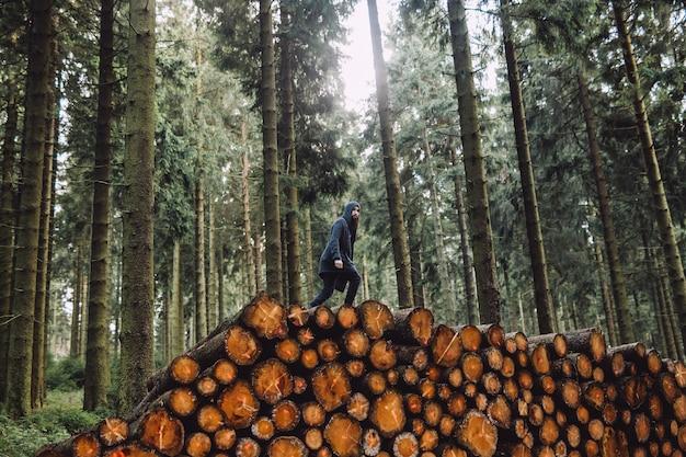 L'uomo con la barba va sul legno nella foresta