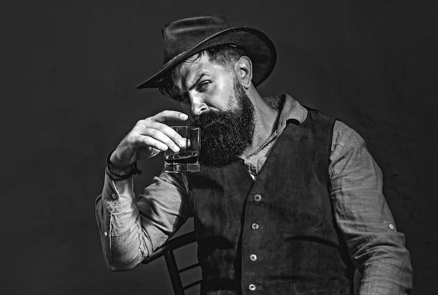 Uomo con la barba che tiene un bicchiere di brandy