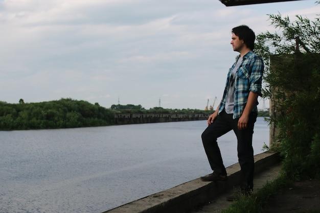 Un uomo con la barba e in jeans si trova nella zona industriale