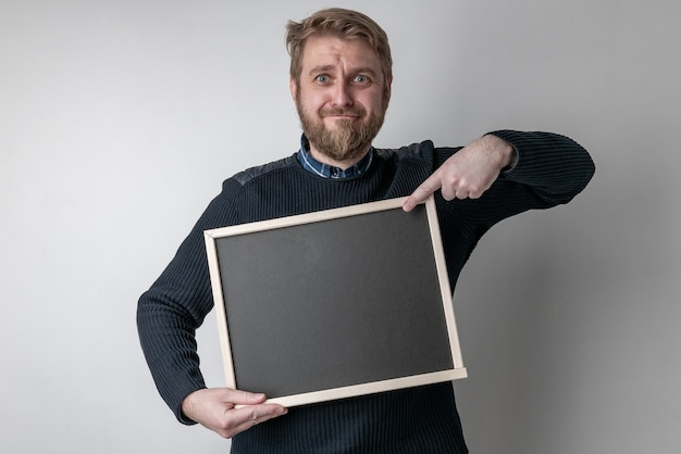 Uomo con la barba che punta sulla lavagna vuota spaventato in stato di shock con una faccia sorpresa, spaventato ed eccitato con l'espressione di paura