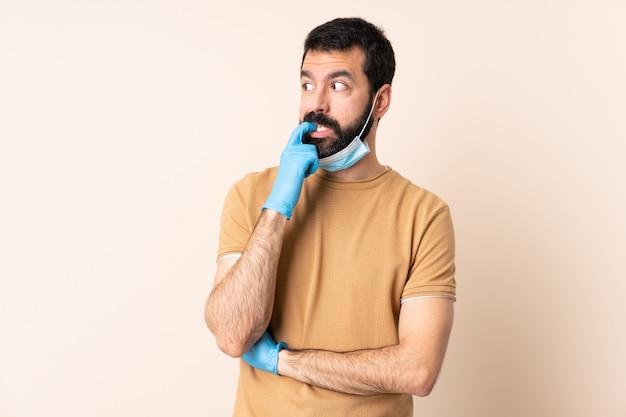 Uomo con la barba che protegge dal coronavirus con una maschera e guanti sopra la parete isolata nervosa e spaventata