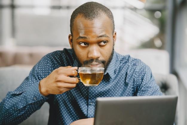 Uomo con la barba seduto in un bar e bere un tè