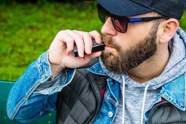 L'uomo con la barba fuma una sigaretta elettronica in un parco