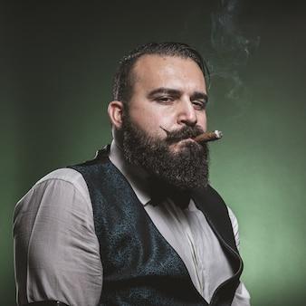 Uomo con la barba che fuma un sigaro, guardando la telecamera.