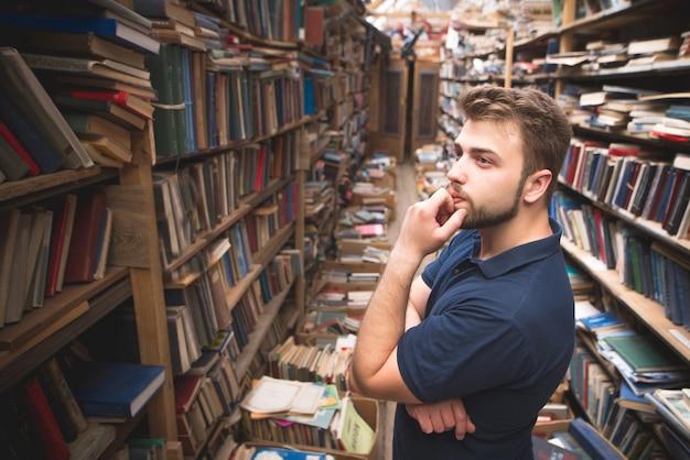 Uomo con la barba in piedi su una biblioteca pubblica e guardando lo scaffale