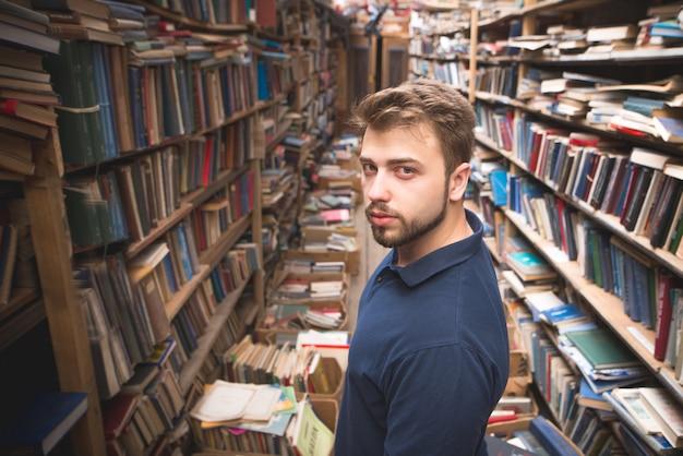 Uomo con la barba in piedi su una biblioteca pubblica