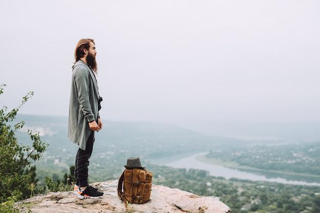 L'uomo con la barba si trova su una scogliera con un bellissimo paesaggio estivo.