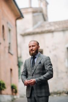 Un uomo con la barba in un rigoroso abito grigio a tre pezzi con cravatta nel centro storico di sirmione, un uomo elegante con un abito grigio in italia.