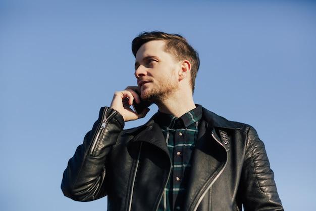 Uomo con la barba che parla sul suo smartphone