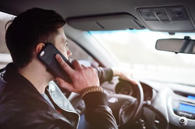 Un uomo con la barba che parla su un telefono cellulare in macchina.