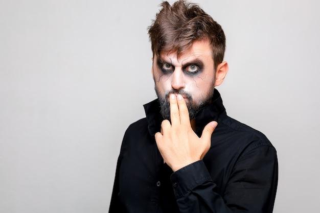 Un uomo con la barba e il trucco da non morto ad halloween tiene le mani davanti a sé